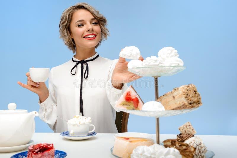 Stående av den unga härliga flickan med sötsaker över blå bakgrund royaltyfri fotografi