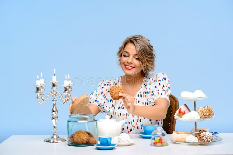 Stående av den unga härliga flickan med sötsaker över blå bakgrund arkivfoto