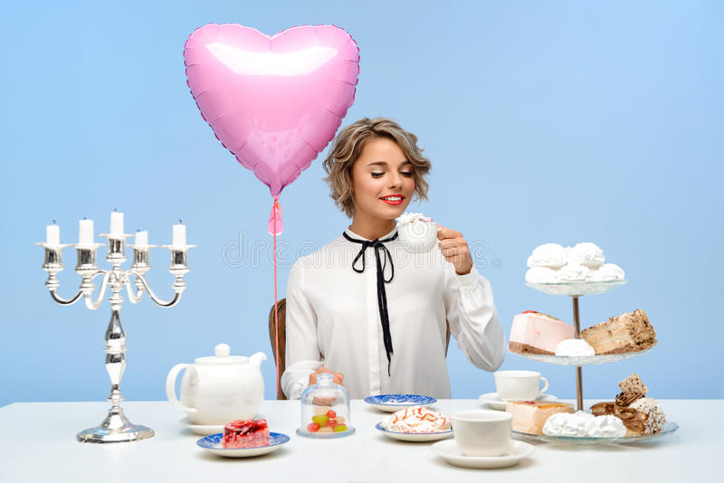 Stående av den unga härliga flickan med sötsaker över blå bakgrund royaltyfria foton