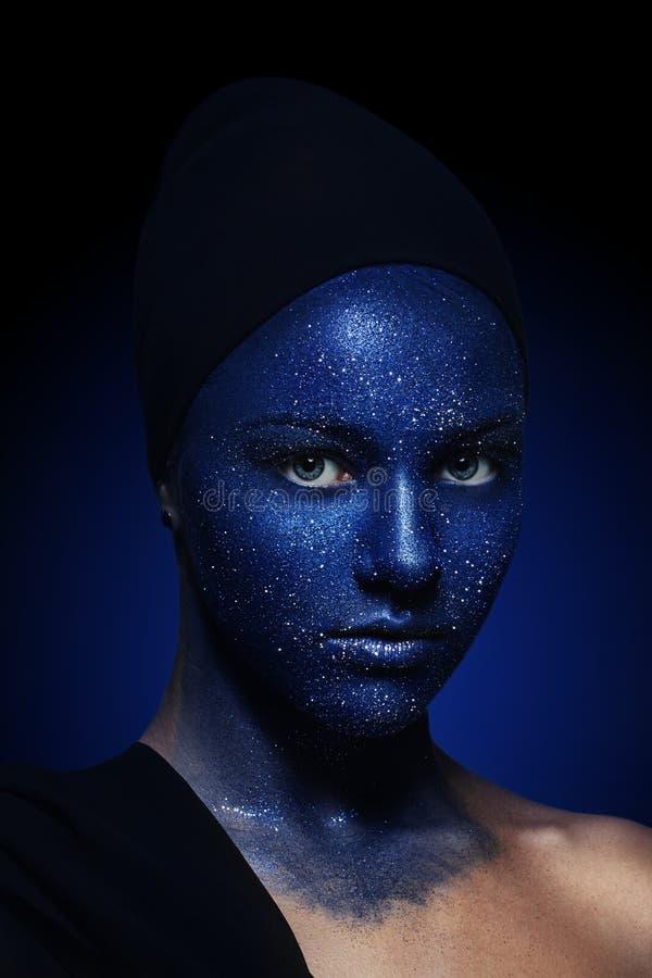 Stående av den unga härliga flickan vända mot målat med blåttmålarfärg och blänka royaltyfri foto