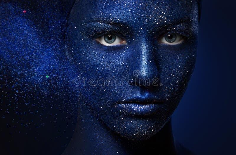 Stående av den unga härliga flickan vända mot målat med blåttmålarfärg och blänka arkivfoto