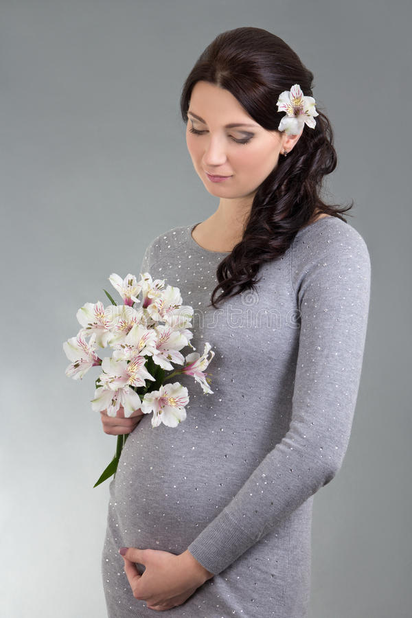 Stående av den unga härliga gravida kvinnan med blommor över gre royaltyfri fotografi