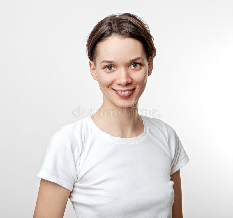 Stående av den unga härliga gulliga gladlynta flickan som ler se kameran som isoleras på vit bakgrund arkivbild