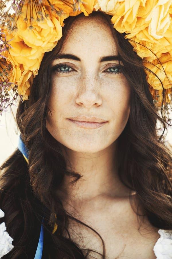Stående av den unga härliga kvinnaarmringen av blommor på huvudet arkivfoto
