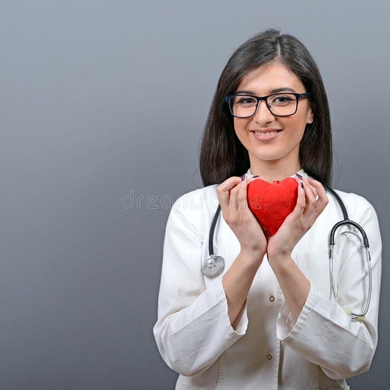 Stående av den unga härliga kvinnadoktorn som rymmer röd hjärta mot grå bakgrund royaltyfri bild