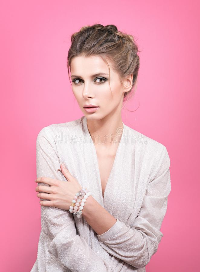 Stående av den unga härliga kvinnan i ett ljus - grå blus Armband eller pärlor förestående arkivfoto