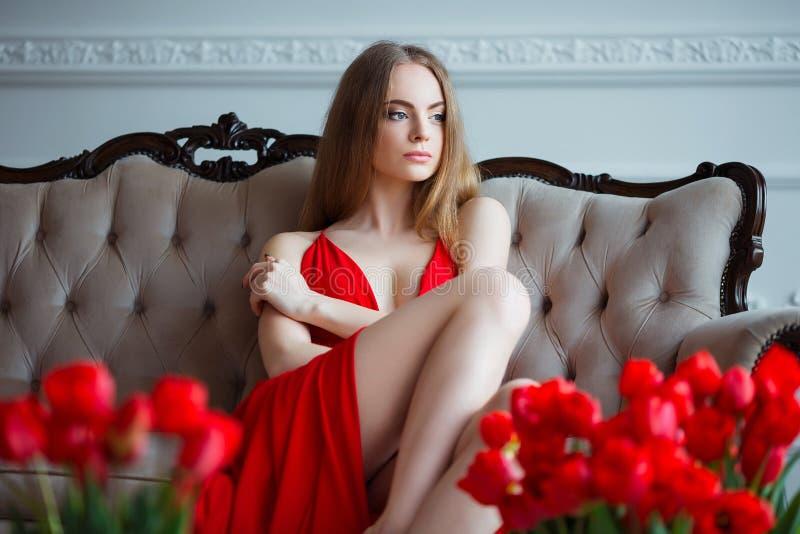 Stående av den unga härliga kvinnan i röd klänning med tulpan i lyxig inre royaltyfria bilder