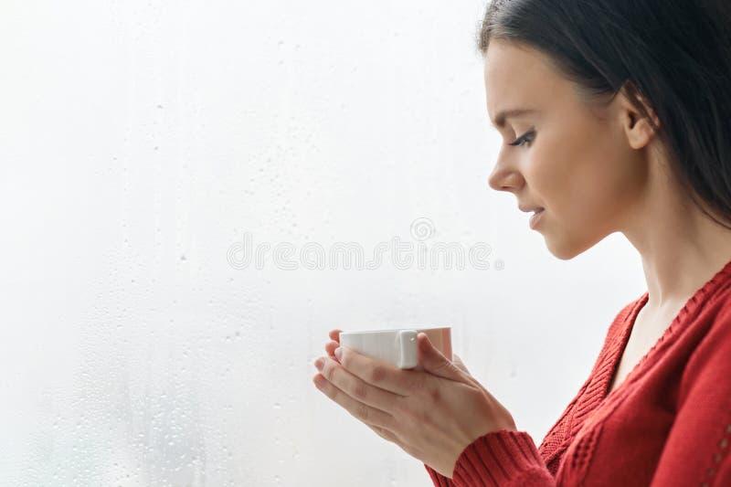 Stående av den unga härliga kvinnan i röd tröja som dricker kaffe Kvinnligt anseende nära fönster i skyskrapa i morgon på molnigt royaltyfria bilder