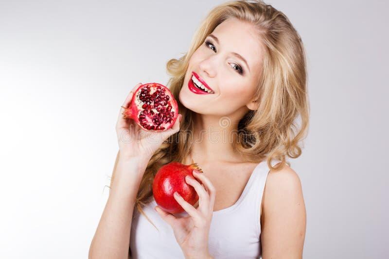 Stående av den unga härliga kvinnan med granatäpplen royaltyfri foto