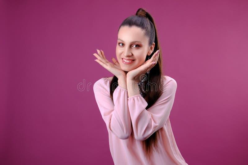 Stående av den unga härliga kvinnan med ljus makeup som trycker på hennes framsida Rosa bakgrund arkivbilder