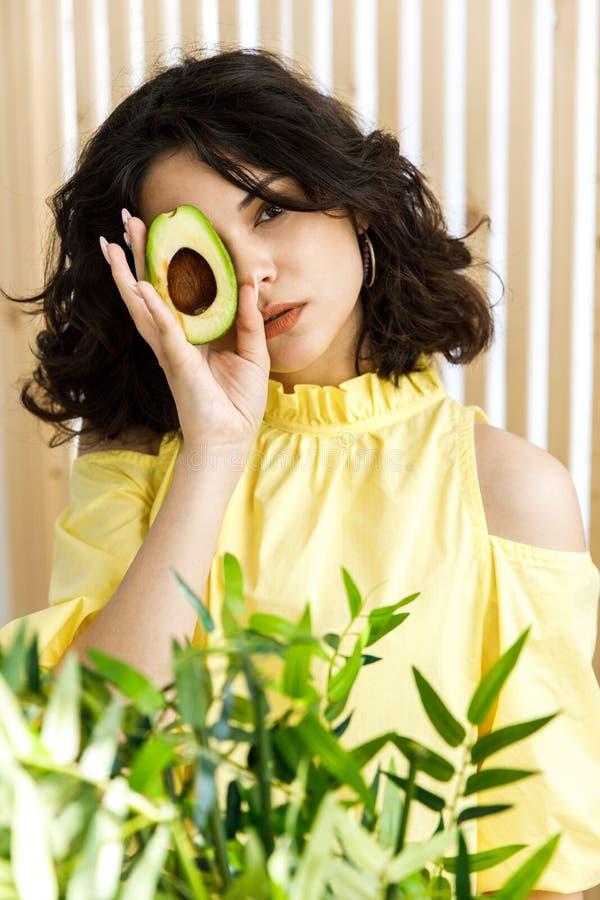 Stående av den unga härliga kvinnan med den mogna läckra avokadot på ljus bakgrund sund mat fotografering för bildbyråer