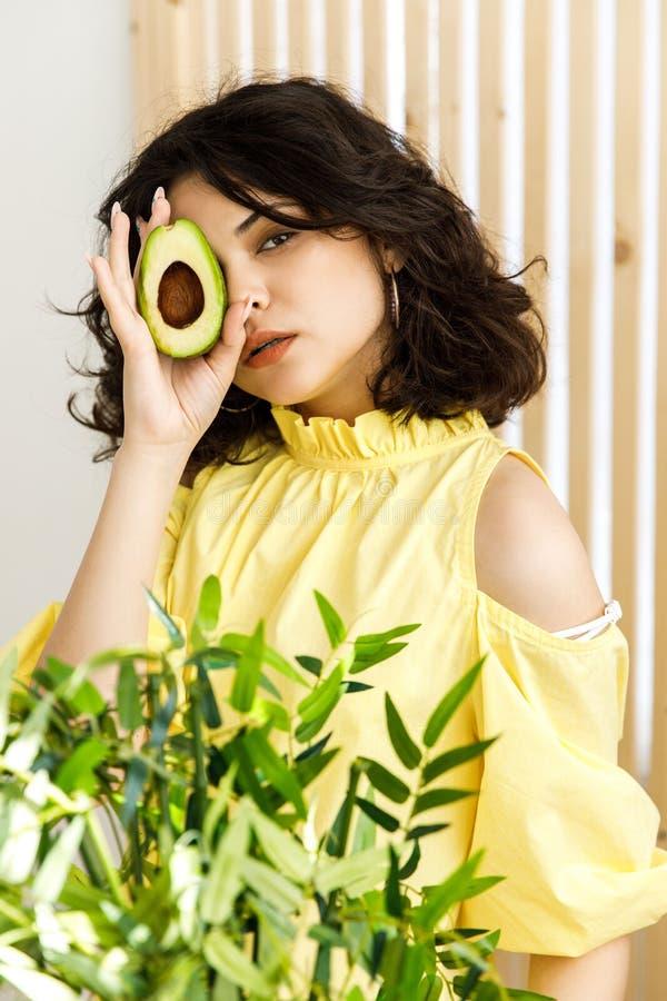 Stående av den unga härliga kvinnan med den mogna läckra avokadot på ljus bakgrund sund mat royaltyfri foto