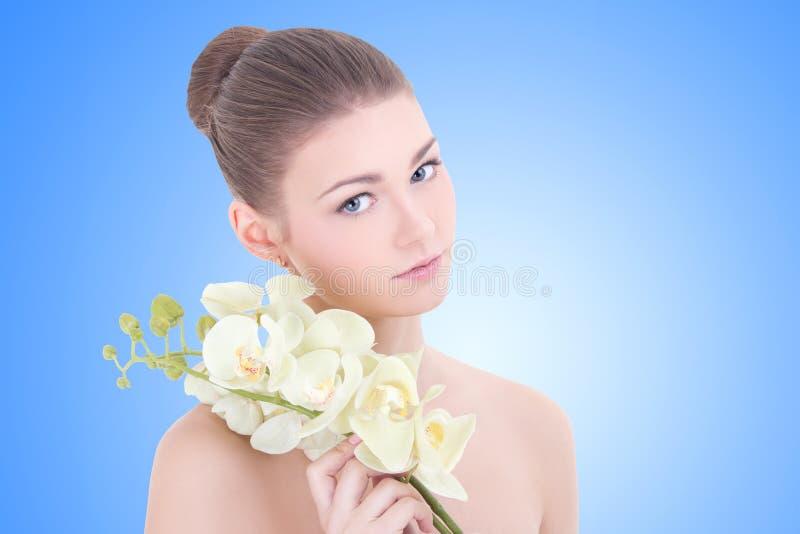 Stående av den unga härliga kvinnan med orkidéblomman över blått royaltyfri bild