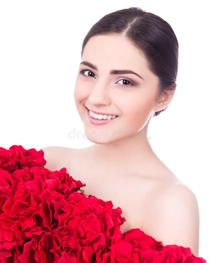 Stående av den unga härliga kvinnan med röda blommor som isoleras på w royaltyfria bilder