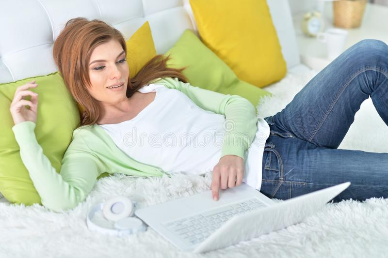 Stående av den unga härliga kvinnan som hemma kopplar av i säng, genom att använda bärbara datorn royaltyfria foton