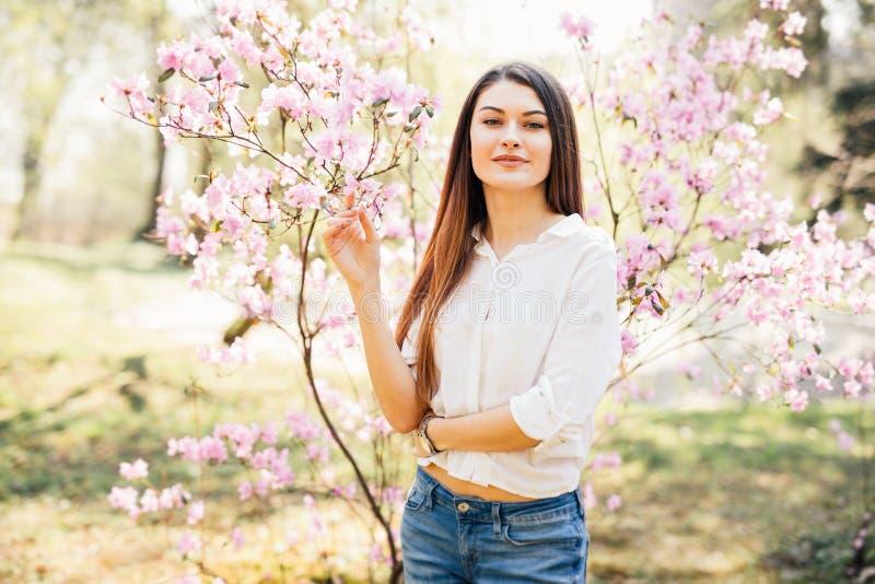 Stående av den unga härliga kvinnan som poserar bland blommande träd royaltyfri foto