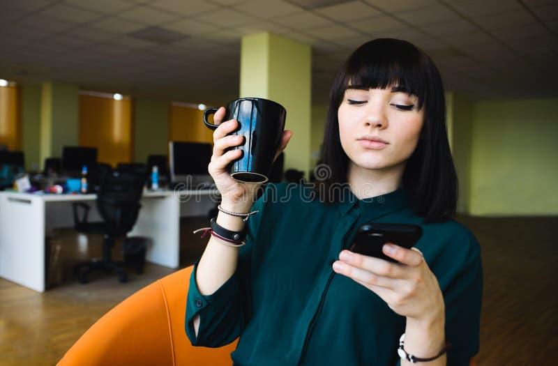 Stående av den unga härliga kvinnliga kontorsarbetaren som använder en mobiltelefon och ett innehav per koppen av drinken arkivfoton