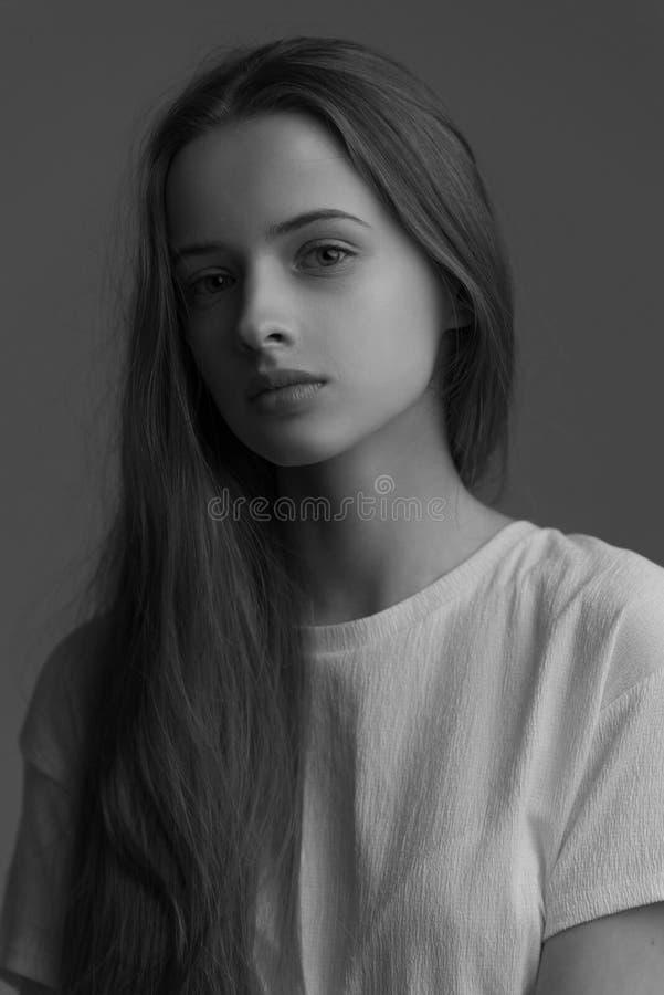 Stående av den unga härliga le flickan med brunt hår i staden royaltyfri foto
