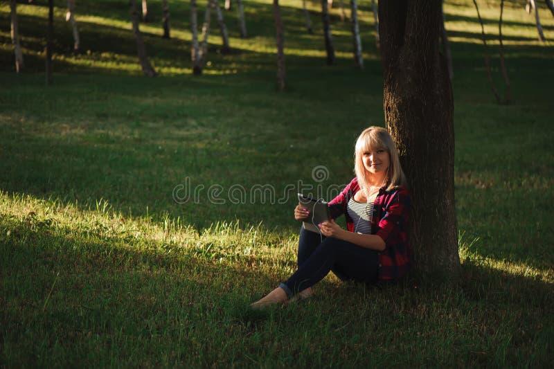 Stående av den unga härliga le kvinnan med minnestavlaPC, utomhus royaltyfri foto