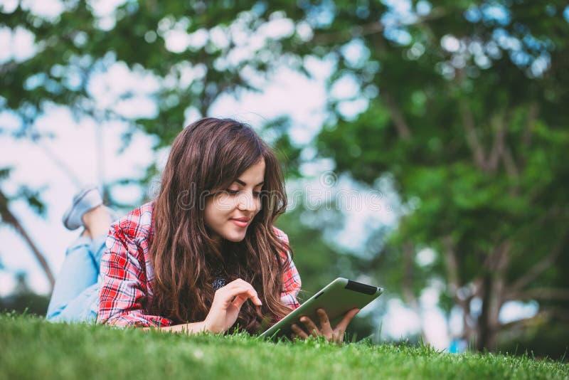 Stående av den unga härliga le kvinnan med minnestavlaPC, utomhus arkivfoto