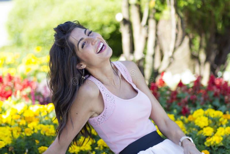 Stående av den unga härliga modekvinnan som skrattar på en blommabakgrund arkivbilder