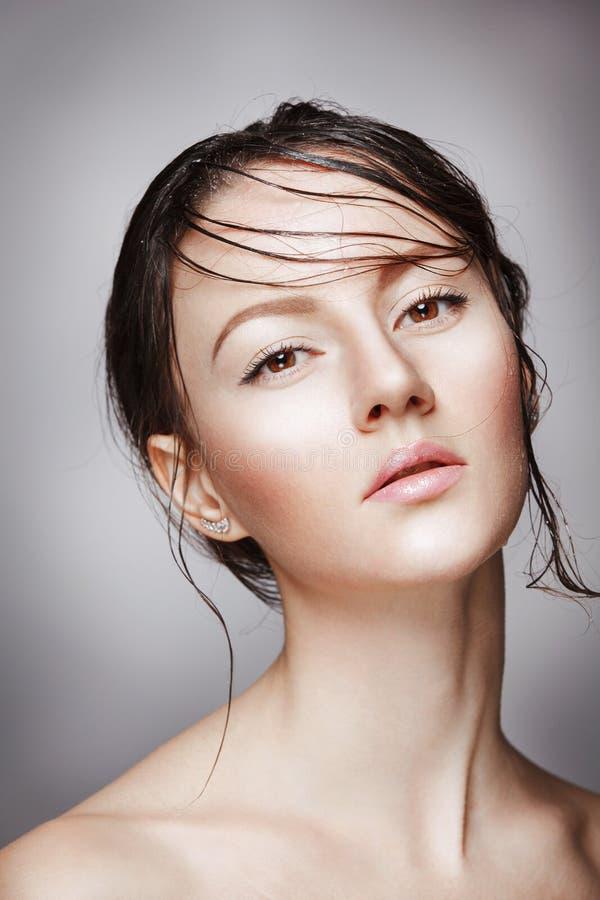 Stående av den unga härliga näcka kvinnan med våt glänsande makeup på grå bakgrund royaltyfria foton