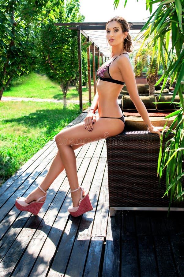 Stående av den unga härliga sexiga kvinnan med långa ben i bikini arkivfoton