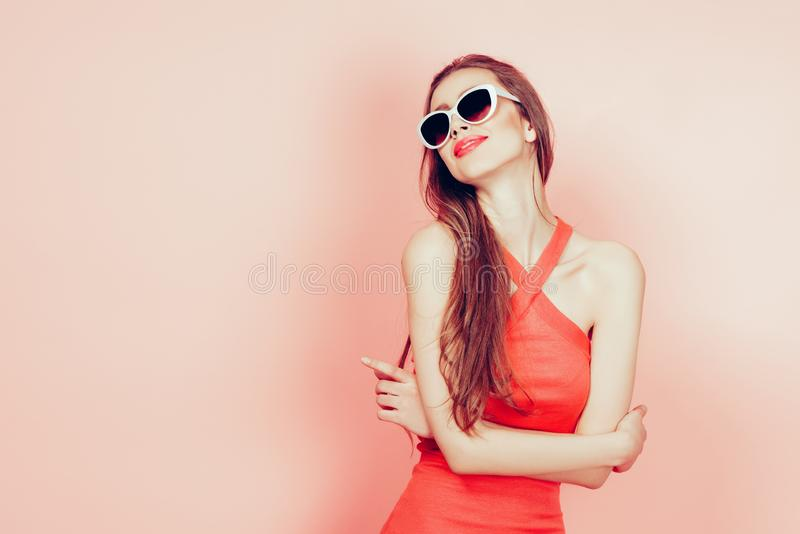 Stående av den unga härliga slanka kvinnan i sexig klänning med sinnliga kanter i bärande solglasögon för studio le och posera arkivbild