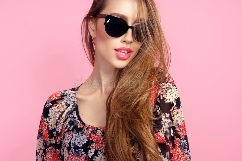Stående av den unga härliga slanka kvinnan i sexig klänning med sinnliga kanter i bärande solglasögon för studio le och posera royaltyfria bilder