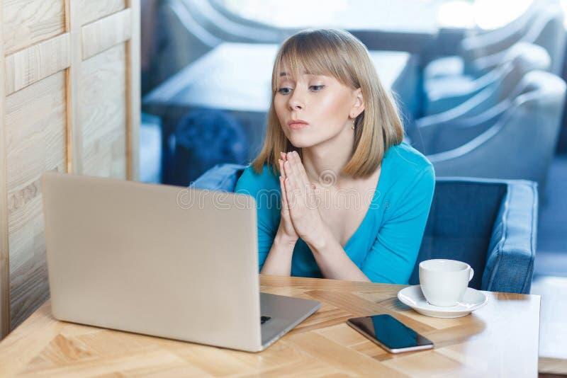 Stående av den unga härliga studenten med blont hår i den blåa t-skjortan som sitter i kafé och talande tankewebcame med gruppkom royaltyfria bilder