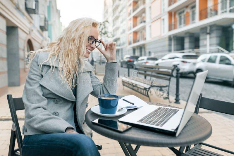 Stående av den unga härliga trendiga blonda kvinnan i varm kläder som sitter i ett utomhus- kafé med bärbar datordatoren, dricka  arkivfoto