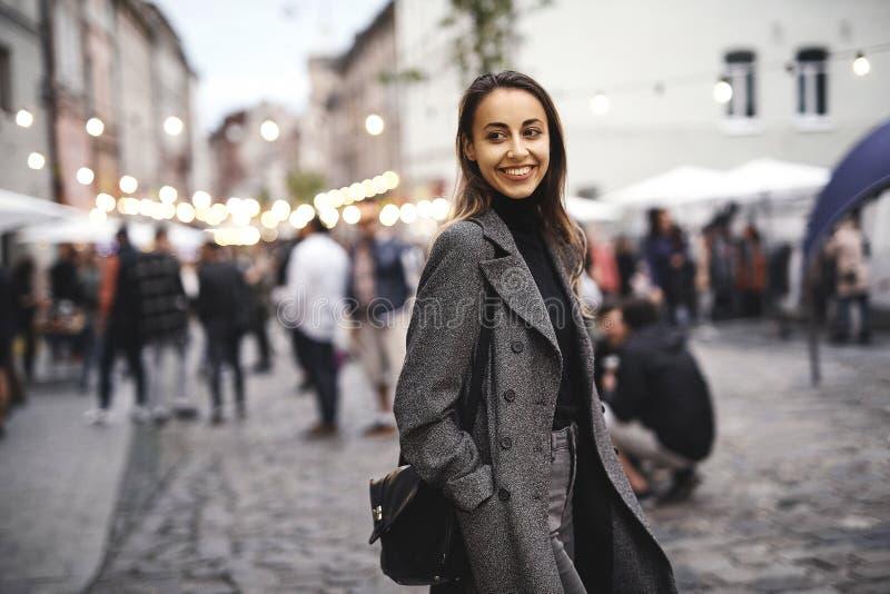 Stående av den unga härliga trendiga brunettkvinnan som poserar i gata på hösten arkivfoto