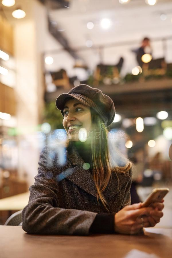 Stående av den unga härliga trendiga brunettkvinnan som sitter i kafé arkivfoton