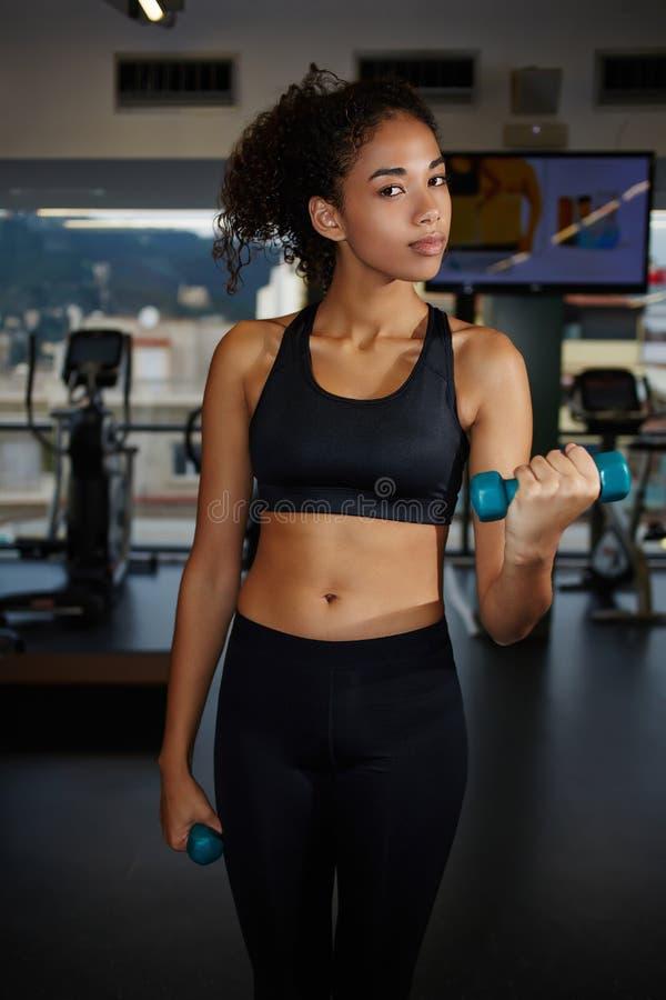 Stående av den unga idrotts- kvinnan som utarbetar med fria vikter på idrottshallen arkivbild