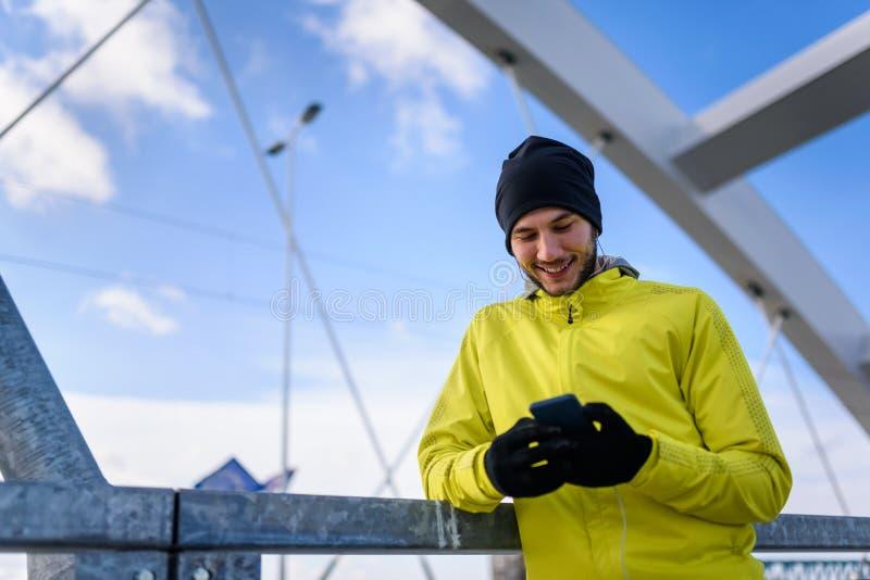 Stående av den unga idrottsman nenmannen i vindtygsjacka genom att använda Smart-telefonen arkivfoto