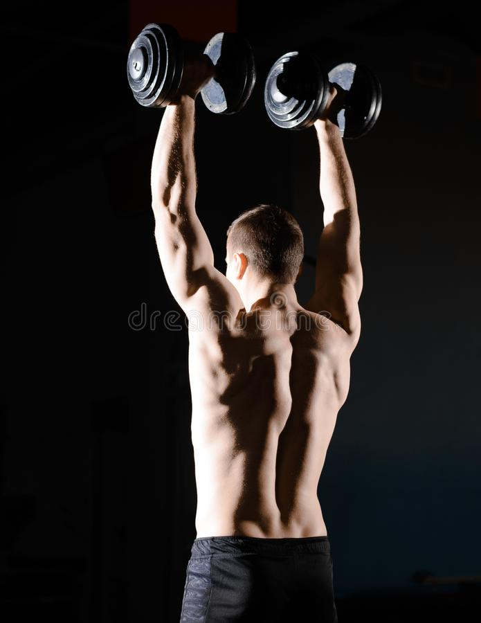 Stående av den unga idrottsmannen som lyfter tunga hantlar i idrottshall Kondition och sunt livsstilbegrepp dramatisk lighting arkivbild