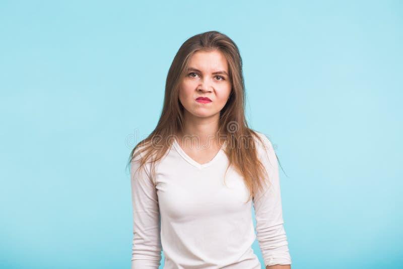 Stående av den unga ilskna kvinnan på blå bakgrund royaltyfria foton