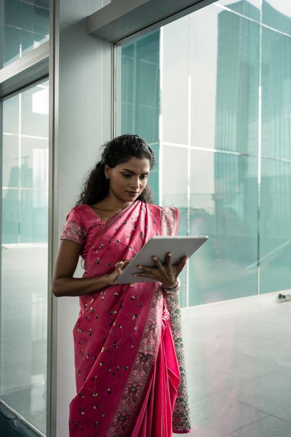 Stående av den unga indiska kvinnan som utomhus använder en minnestavlaPC royaltyfri foto