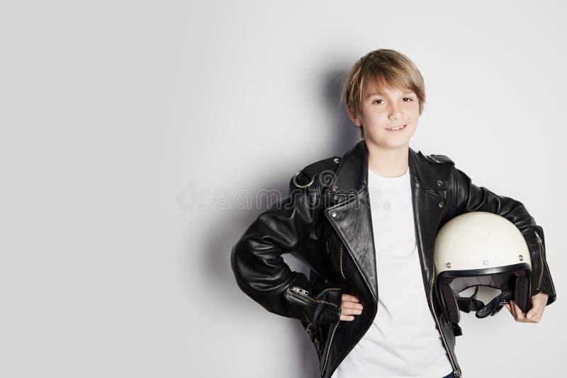 Stående av den unga kalla härliga tonåriga ungen i svart omslag och att rymma för läder den vita motohjälmen för hand som ler på  royaltyfri foto