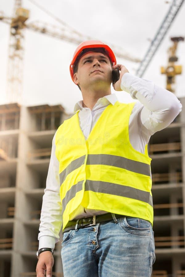 Stående av den unga konstruktionsteknikern som talar vid telefonen på buil royaltyfri fotografi