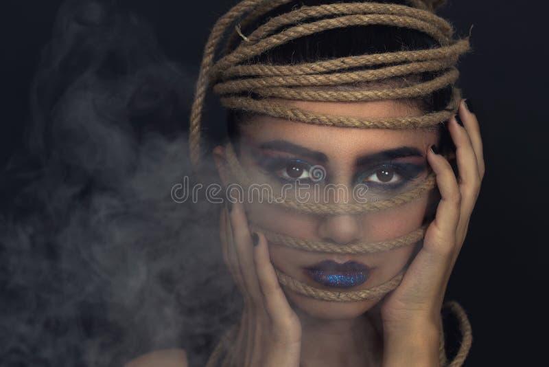 Stående av den unga kvinnan över rep med svart bakgrund Mode, utöver det vanliga makeup och begrepp för lyfta för framsida royaltyfri bild