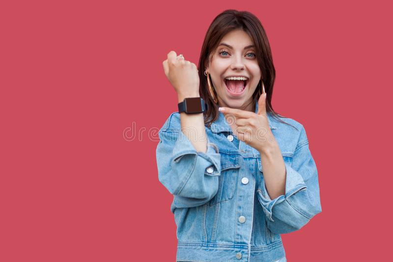 Stående av den unga kvinnan för förvånad lycklig härlig brunett, i visning och att peka för anseende för tillfällig stil för grov arkivbild