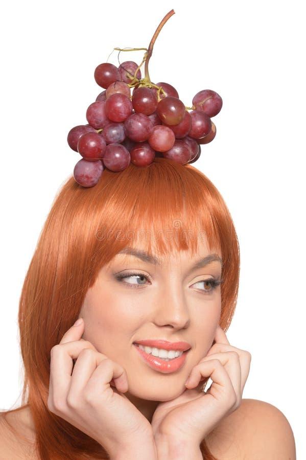 Stående av den unga kvinnan för härlig rödhårig man med röda druvor på huvudet royaltyfria bilder