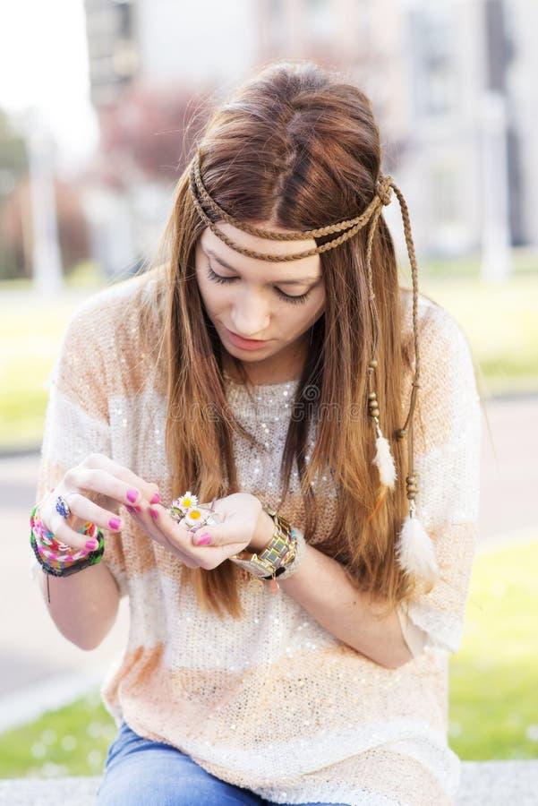 Stående av den unga kvinnan för hippie som spelar med tusenskönor. arkivbild