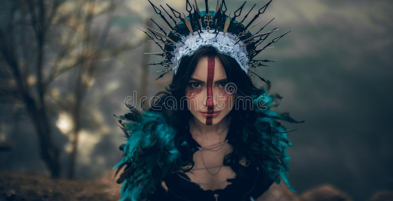 Stående av den unga kvinnan i bilden av en fe och ett trollkvinnaanseende över en sjö arkivbild