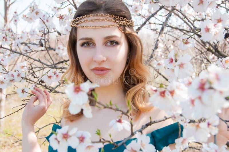 Stående av den unga kvinnan i den blommiga trädgården royaltyfria bilder