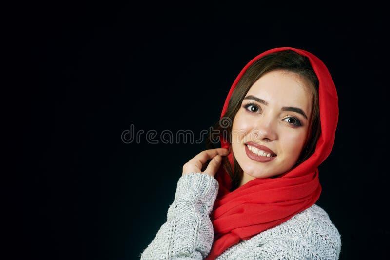Stående av den unga kvinnan i hatt och omslag på mörk bakgrund royaltyfria bilder