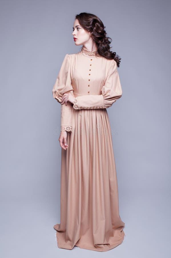 Stående av den unga kvinnan i retro klänning arkivfoto