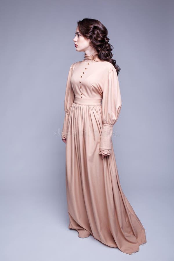 Stående av den unga kvinnan i retro klänning arkivfoton