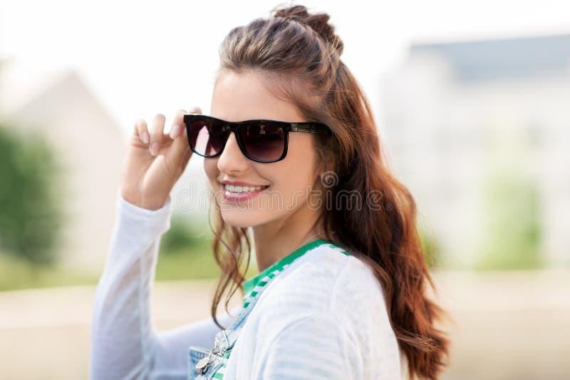 Stående av den unga kvinnan i solglasögon utomhus arkivfoton